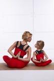 照顾做瑜伽锻炼,健身,健身房的女儿佩带同样舒适的田径服,家庭体育,被配对的体育 库存图片