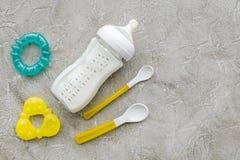 照顾关心在瓶和婴儿惯例搽粉的健康食物和玩具的乳奶哺养在石背景的婴孩的 免版税图库摄影