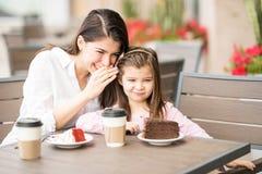照顾告诉秘密给她的女儿在餐馆 库存图片