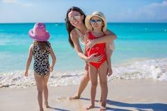 照顾和两个小孩在海滩在晴天 免版税图库摄影