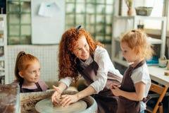 照顾和两个红头发人女儿做有瓦器轮子的黏土杯子 库存照片
