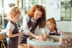 照顾和两个红头发人女儿做有瓦器轮子的黏土杯子 免版税图库摄影