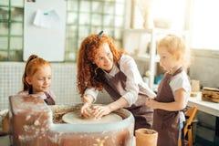 照顾和两个红头发人女儿做有瓦器轮子的黏土杯子 图库摄影