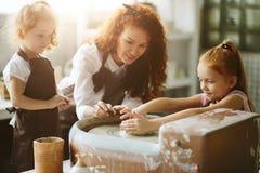 照顾和两个红头发人女儿做有瓦器轮子的黏土杯子 免版税库存图片