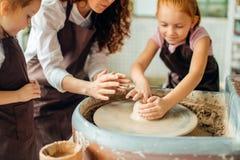 照顾和两个红头发人女儿做有瓦器轮子的黏土杯子 免版税库存照片
