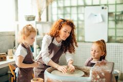 照顾和两个红头发人女儿做有瓦器轮子的黏土杯子 库存图片