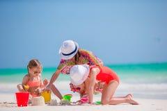 照顾和使用与在热带海滩的沙子的两个孩子 家庭做一座新的城堡 库存图片