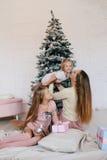 照顾和在家使用在圣诞树附近的两个女儿 愉快的家庭获得乐趣为圣诞节假日 图库摄影