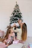 照顾和在家使用在近圣诞树的两个女儿 愉快的家庭获得乐趣为圣诞节假日 免版税库存照片