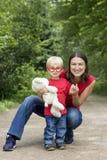 照顾和她戴长毛绒熊和玩具眼镜的逗人喜爱的小孩儿子 免版税库存图片