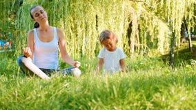 照顾和她的一起做瑜伽锻炼的小逗人喜爱的女儿 库存图片