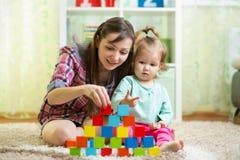 照顾和她的与玩具的孩子戏剧户内 库存照片