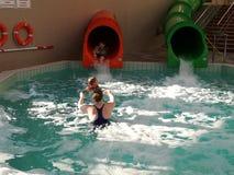 照顾和她的两个孩子对在水池的幻灯片 库存照片