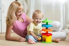 照顾和她的使用与五颜六色的逻辑玩具的孩子 免版税库存照片