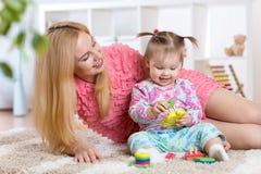 照顾和她的使用与五颜六色的难题玩具的孩子 免版税库存照片