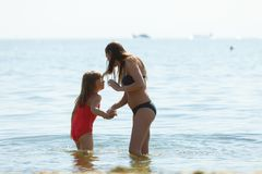 照顾和她的使用在海滩的小孩女儿 免版税库存照片