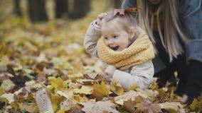 照顾和她的使用在秋天公园的女儿小女孩-投掷叶子,婴孩笑声 库存照片