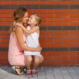 照顾和她的使用户外在夏天的女儿 免版税库存图片