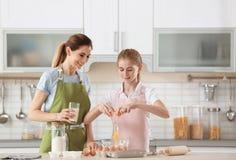 照顾和她的做面团的女儿在桌上 免版税库存图片