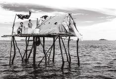 照顾和她的坐他们的小帐篷房子外的女儿漂浮在Semporna海,沙巴Semporna,马来西亚 图库摄影