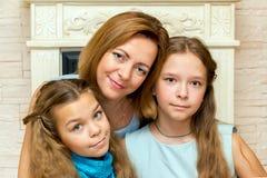 照顾和她的坐在壁炉附近的两个女儿 库存图片