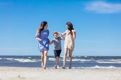 照顾和她的孩子有步行由海 免版税库存照片