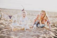照顾和她的小儿子在海滩 库存照片