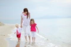 照顾和她的走沿海滩的孩子 免版税图库摄影