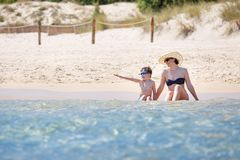 照顾和她的飞溅在海浪的小儿子 库存照片