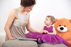 照顾和她的紫罗兰色礼服的好奇女儿有玩具熊的 库存图片