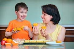 照顾和她逗人喜爱的小男孩烘烤松饼 免版税库存照片