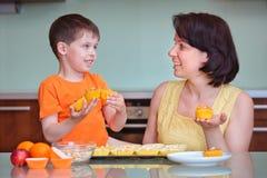 照顾和她逗人喜爱的小男孩烘烤松饼 免版税库存图片
