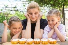 照顾和有好看复活节杯形蛋糕的胃口和大眼睛的两个女儿 免版税库存照片