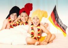 照顾和欢呼与德国旗子的两个儿子 免版税库存图片