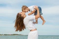 照顾和获得她的儿子在海滩的乐趣 图库摄影