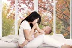 照顾和获得她的婴孩在床上的乐趣 免版税库存照片