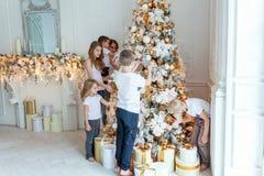 照顾和装饰圣诞树的五个孩子 图库摄影