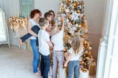 照顾和装饰圣诞树的五个孩子 库存图片