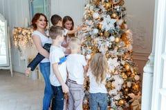 照顾和装饰圣诞树的五个孩子 库存照片