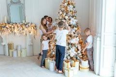照顾和装饰圣诞树的五个孩子 免版税图库摄影