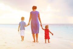 照顾和走在海滩的两个孩子 免版税库存图片