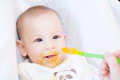 照顾喂养她有匙子的可爱的男婴 免版税图库摄影