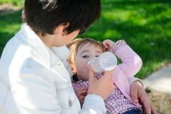 照顾喂养有哺乳瓶的一个年女婴 图库摄影
