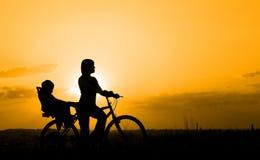 照顾在一辆自行车的骑马有她的孩子的 库存照片