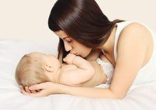 照顾在家亲吻她的在床上的婴孩 免版税库存图片