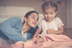 照顾在家教她的女儿对阅读书 免版税图库摄影