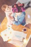 照顾她的孩子的繁忙的妈妈 免版税图库摄影
