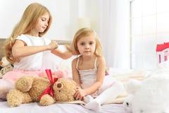 照顾她的小兄弟姐妹的更老的孩子 免版税库存图片