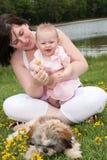 照顾她的婴孩和花 免版税库存图片