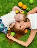 照顾妇女和女儿儿童婴孩躺下孩子的女孩 免版税图库摄影